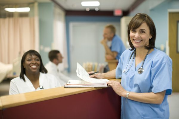 travel nurse credentialing - 5 things to know - featured image of nurses reviewing credentialing paperwork