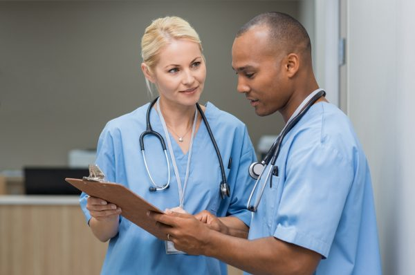 ways to get promoted - featured image of nurses reviewing medical records on a travel assignment