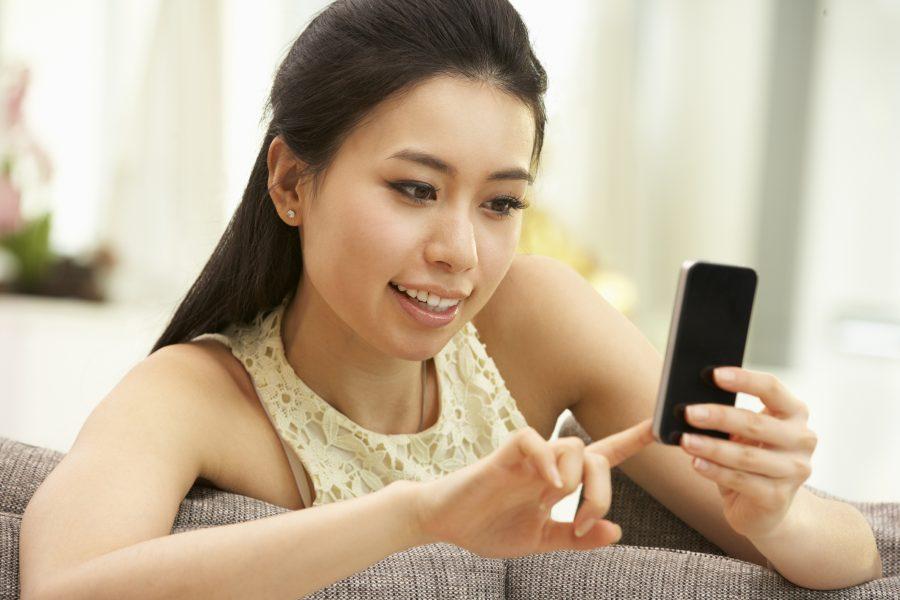 RNnetwork - travel nurse job seeker social media profiles - featured image of nurse making a mobile social medial post