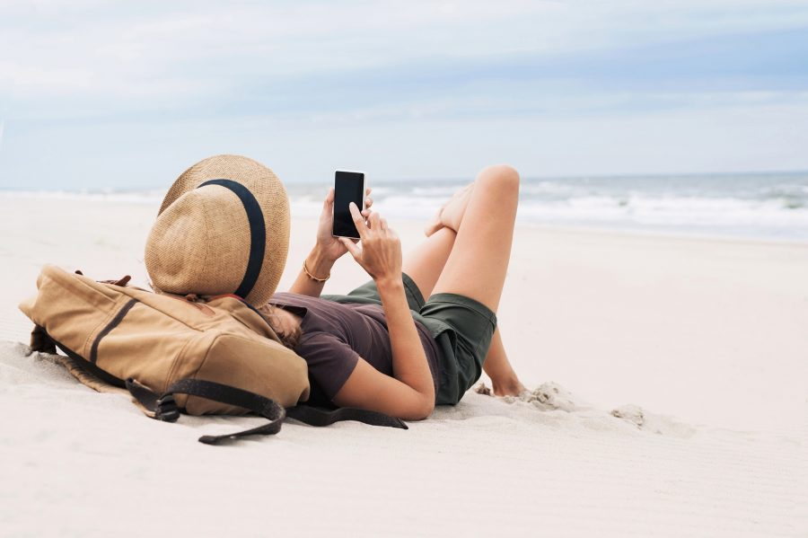RNnetwork - apply for a travel nursing job - featured image of travel nurse on a beach using mobile device to book her next assignment
