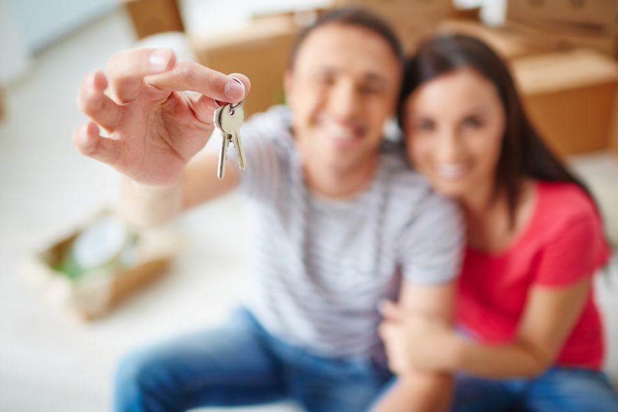 RNnetwork - agency housing for travel nurses - featured image of travel nurse and spouse with keys to their new apartment