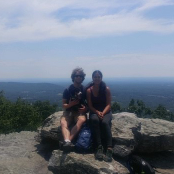 two people sitting on a rock with mountains behind them