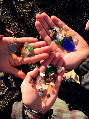 Three hands holding sea glass with sand in background