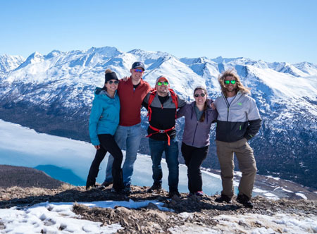 Group of people pose on a snowy mountaintop