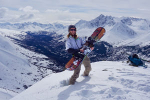 Man standing on a mountain with a snowboard