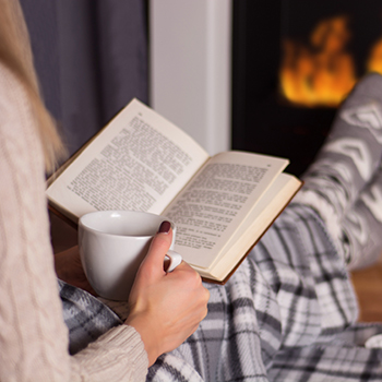 Woman reads book in front of the fire