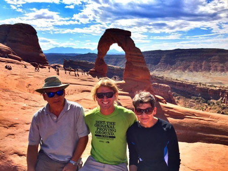 Three people standing in foreground with Delicate Arch in background