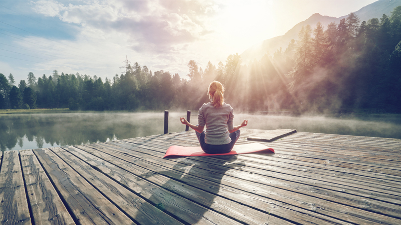 Woman sitting on yoga mat on a pier near a lake