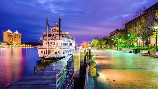 Steamboat docked along river shore at night