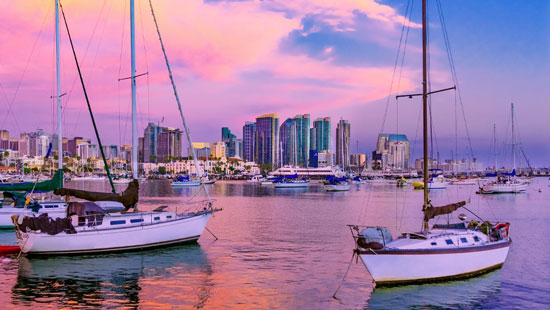 Boats in harbor with pink sunset