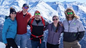 Group of skiers pose for photo in front of mountains