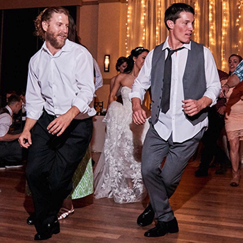 Two men dance at a wedding