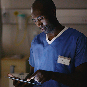 Nurse looking at a tablet in low light